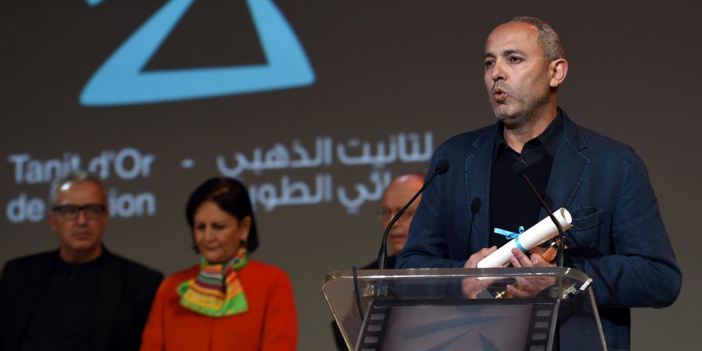 """Moroccan director Mohamed Mouftakir delivers a speech after receiving the Golden Tanit award for his film """"L'orchestre des aveugles"""" during the closing ceremony of the 26th Carthage Film Festival on November 28, 2015 in the Tunisian capital Tunis. AFP PHOTO / FETHI BELAID / AFP / FETHI BELAID"""